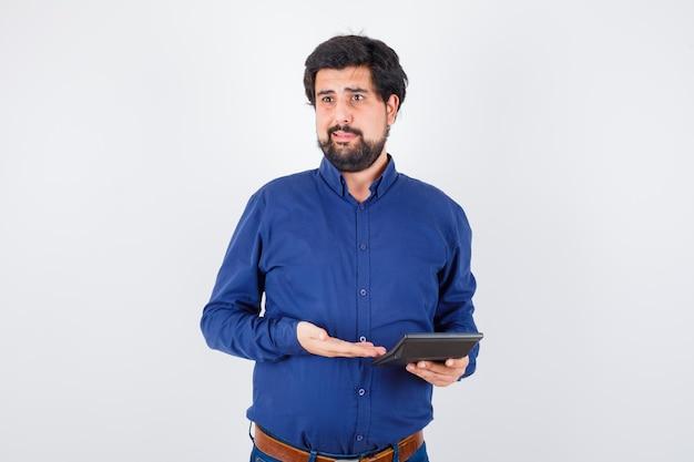 Młody mężczyzna pokazuje kalkulator w królewskiej niebieskiej koszuli, widok z przodu.