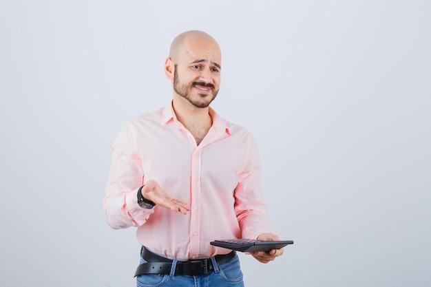 Młody mężczyzna pokazuje kalkulator w różowej koszuli, dżinsach, widok z przodu.