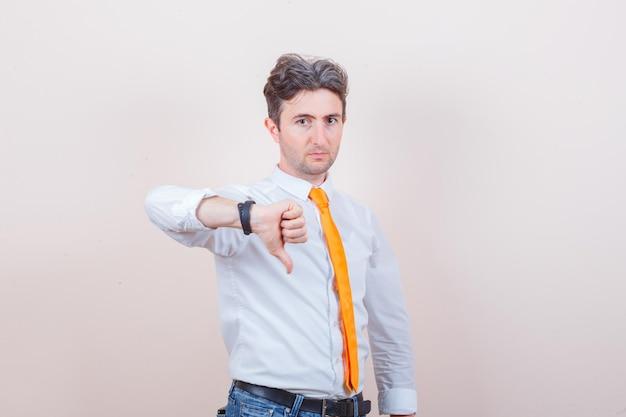 Młody mężczyzna pokazuje kciuk w białej koszuli, krawacie i dżinsach i wygląda pewnie