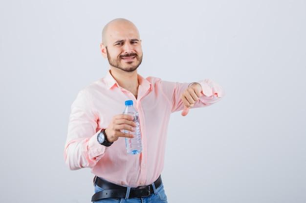 Młody mężczyzna pokazuje kciuk w dół w koszuli, dżinsach i niezadowolony. przedni widok.