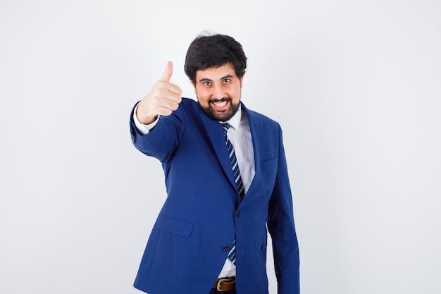 Młody mężczyzna pokazuje kciuk w koszuli, kurtce, krawacie i patrząc wesoło, widok z przodu.