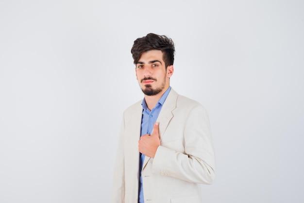 Młody mężczyzna pokazuje kciuk w niebieskiej koszulce i białej marynarce i wygląda poważnie