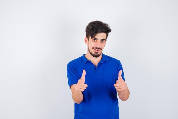 Młody mężczyzna pokazuje kciuki do góry obiema rękami w niebieskiej koszulce i wygląda poważnie
