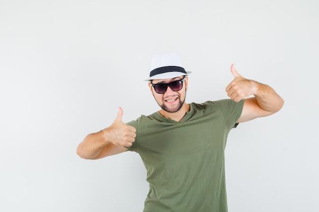 Młody mężczyzna pokazuje kciuki w zielonej koszulce i kapeluszu i wygląda optymistycznie