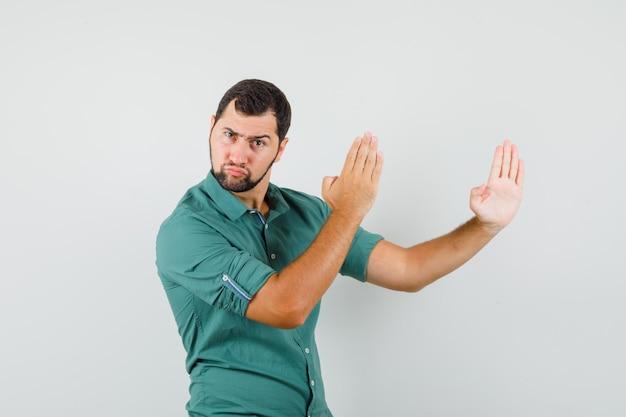 Młody mężczyzna pokazuje kotlet karate w zielonej koszuli i wygląda na potężny. przedni widok.