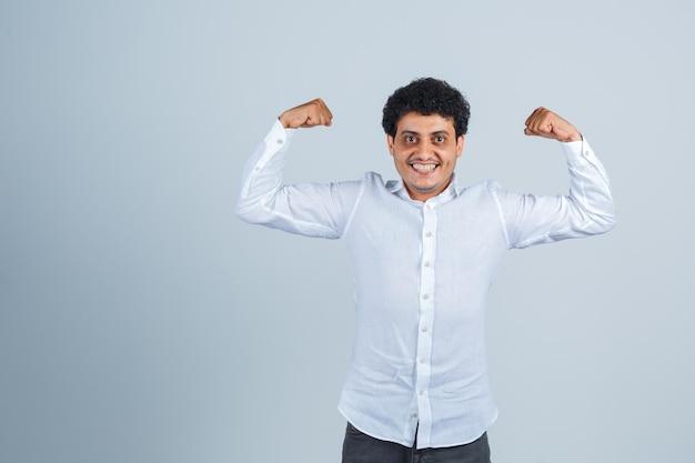 Młody mężczyzna pokazuje mięśnie ramion w białej koszuli i wygląda na potężny, widok z przodu.