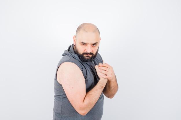 Młody mężczyzna pokazuje mięśnie ramion w bluzie z kapturem bez rękawów i wygląda pewnie, widok z przodu.