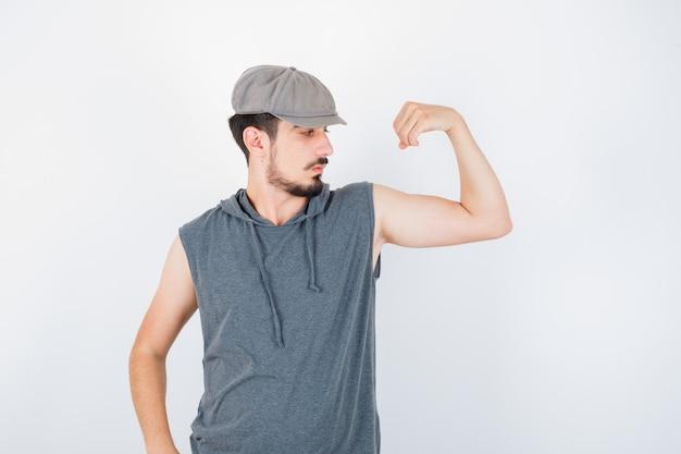 Młody mężczyzna pokazuje mięśnie w szarej koszulce i czapce i wygląda poważnie