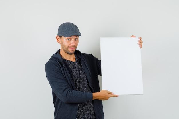Młody mężczyzna pokazuje puste płótno i uśmiecha się w t-shirt, kurtkę, widok z przodu czapki.