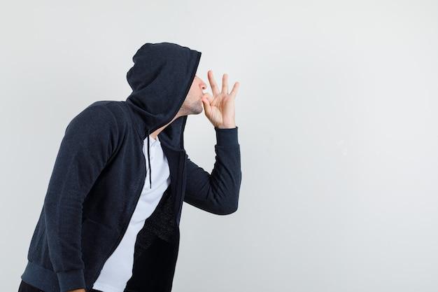 Młody mężczyzna pokazuje pyszny gest w koszulce, kurtce i wygląda zachwycony.