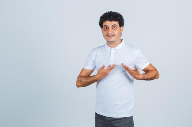 Młody mężczyzna pokazuje się w geście przesłuchania w białej koszulce, spodniach i wygląda na dumnego. przedni widok.