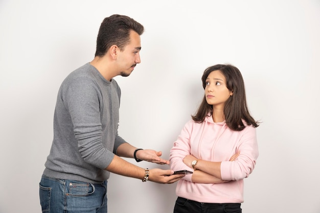 Młody mężczyzna pokazuje swój telefon do kobiety.