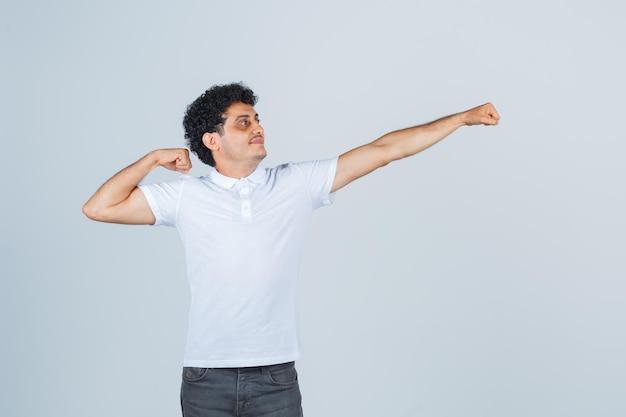 Młody mężczyzna pokazuje tradycyjny gest taneczny w białej koszulce, spodniach i wyglądający elegancko, widok z przodu.