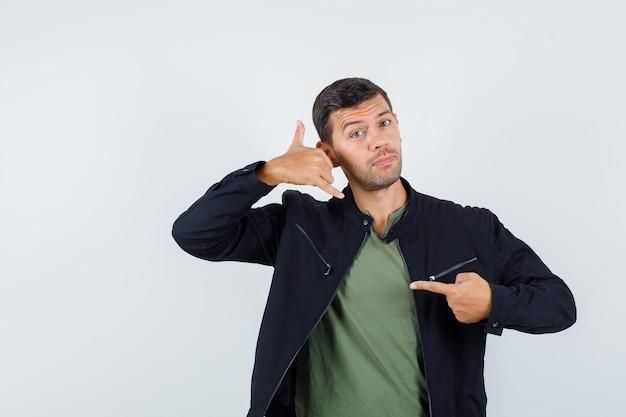Młody mężczyzna pokazuje zadzwoń do mnie gestem w koszulce, kurtce i patrząc pomocny, widok z przodu.