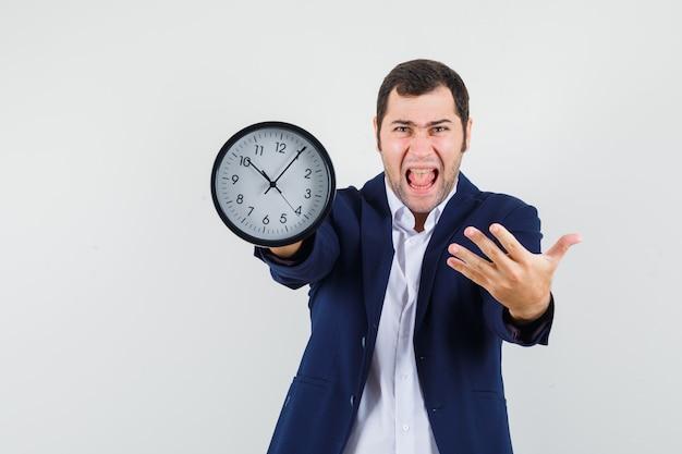 Młody mężczyzna pokazuje zegar ścienny w koszuli i kurtce i szuka wściekłości