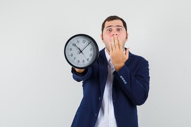 Młody mężczyzna pokazuje zegar ścienny w koszuli i kurtce i wygląda przestraszony