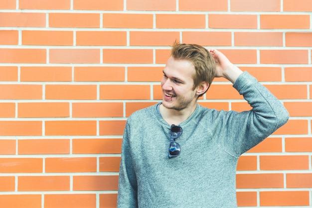 Młody mężczyzna portret przeciw ściana z cegieł