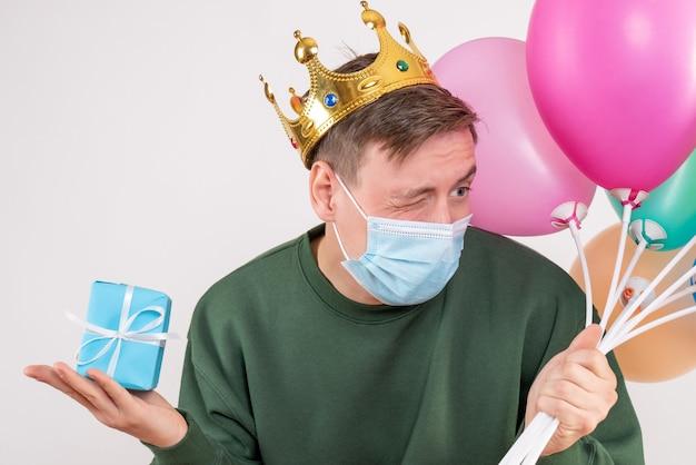 Młody mężczyzna posiadający kolorowe balony i mały prezent na białym tle