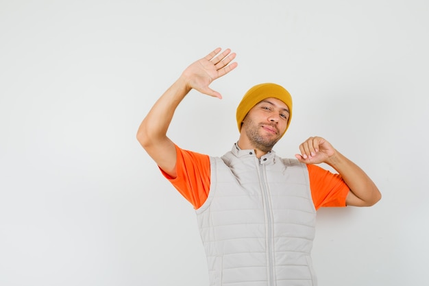 Młody mężczyzna pozowanie, machając ręką w t-shirt, kurtkę, kapelusz i ładny wygląd.