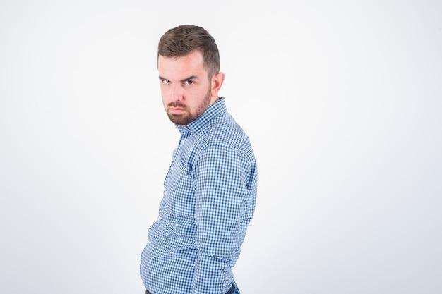 Młody mężczyzna pozowanie, patrząc na kamery w koszuli i patrząc poważny, przedni widok.