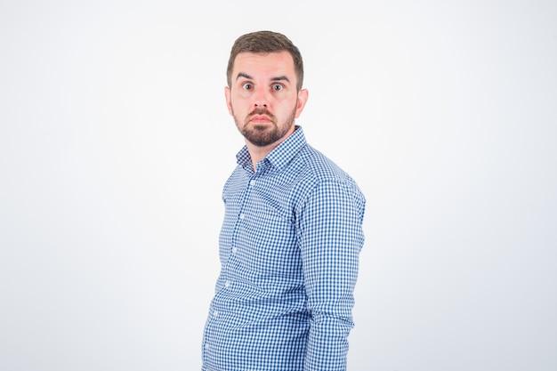 Młody mężczyzna pozowanie, patrząc na kamery w koszuli i wyglądając na zakłopotanego. przedni widok.