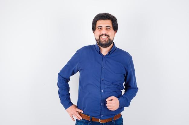 Młody mężczyzna pozowanie stojąc w niebieskiej koszuli i patrząc pewnie. przedni widok.