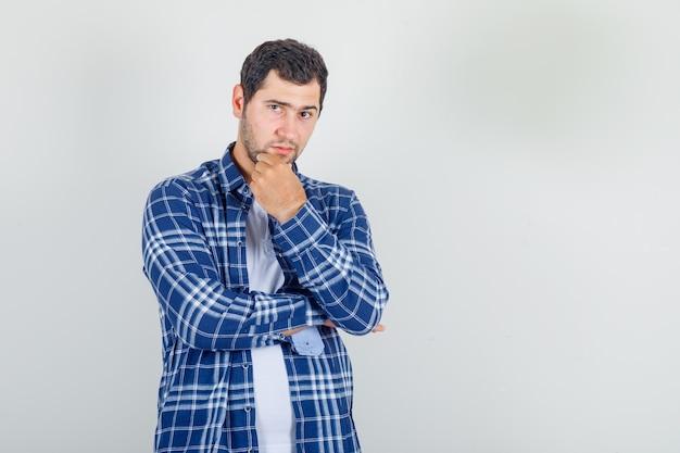 Młody mężczyzna pozowanie z ręką na brodzie w koszuli
