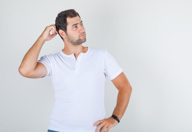 Młody mężczyzna pozowanie z rękami w talii i szyi w białej koszulce