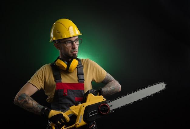 Młody mężczyzna pozujący na czarnym tle w mundurze roboczym i narzędziu budowlanym (piła elektryczna)