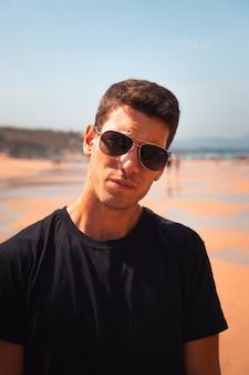 Młody mężczyzna pozuje na plaży ilbarritz w biarritz w kraju basków.