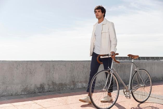 Młody mężczyzna pozuje obok swojego roweru
