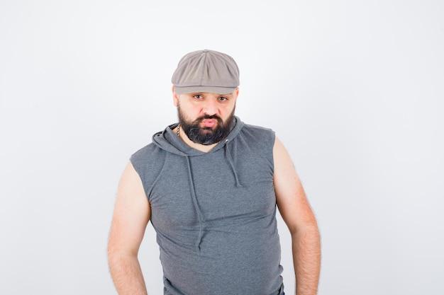 Młody mężczyzna pozuje stojąc w bluzie z kapturem bez rękawów, czapce i patrząc pewnie. przedni widok.