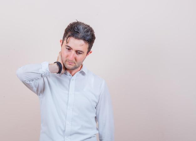 Młody mężczyzna pozuje, trzymając rękę na szyi w białej koszuli i patrząc na zamyślonego