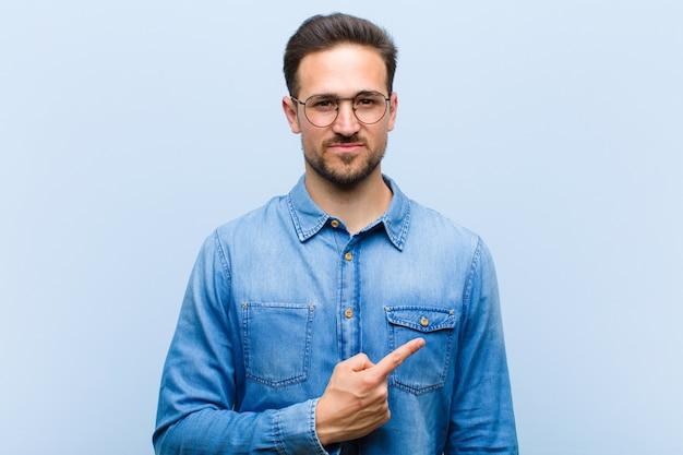 Młody mężczyzna pozuje uśmiechając się i wskazując na siebie lub czyniąc znak numer jeden