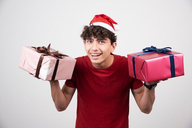 Młody mężczyzna pozuje z pudełkami na prezenty