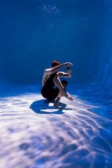 Młody mężczyzna pozuje zanurzony pod wodą