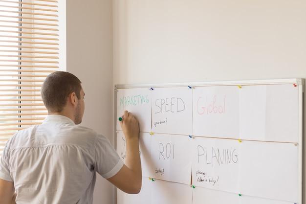 Młody mężczyzna pracownik biurowy pisanie na tablicy do harmonogramu pracy, przymocowany na ścianie budynku wewnętrznego.