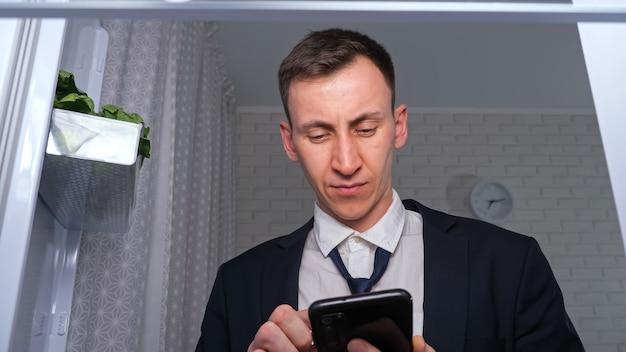 Młody mężczyzna pracownik rozluźnia krawat i robi listę, aby kupić produkty spożywcze na smartfonie w ciemnej kuchni, blisko widoku z wnętrza nowej lodówki
