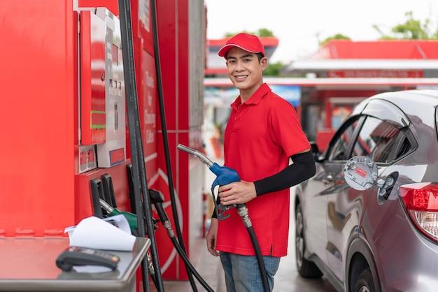 Młody mężczyzna pracownik w czerwonym mundurze trzymający dyszę pompy paliwa zatankować na stacji benzynowej