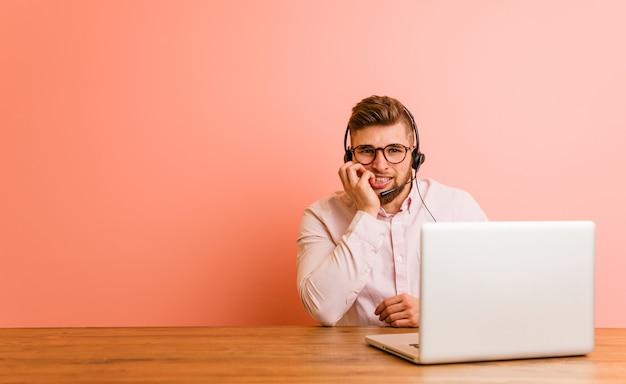 Młody mężczyzna pracujący w call center obgryza paznokcie, jest zdenerwowany i bardzo niespokojny.