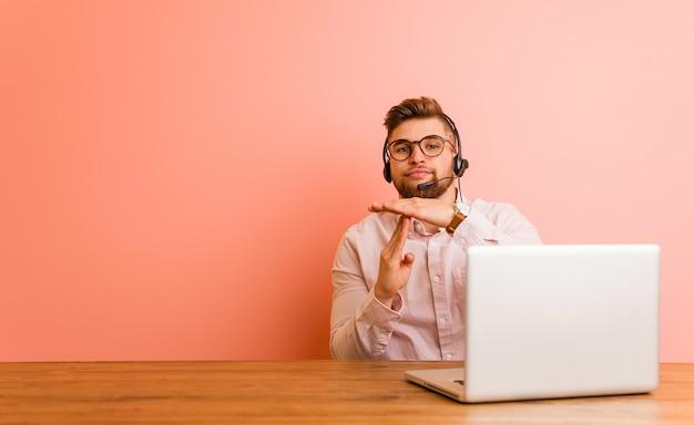 Młody mężczyzna pracujący w call center pokazujący gest limitu czasu.