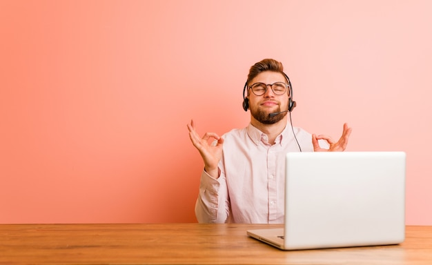 Młody mężczyzna pracujący w call center relaksuje się po ciężkim dniu pracy, wykonuje jogę.
