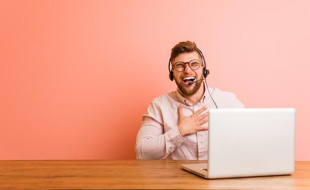 Młody mężczyzna pracujący w call center śmieje się głośno, trzymając rękę na piersi.