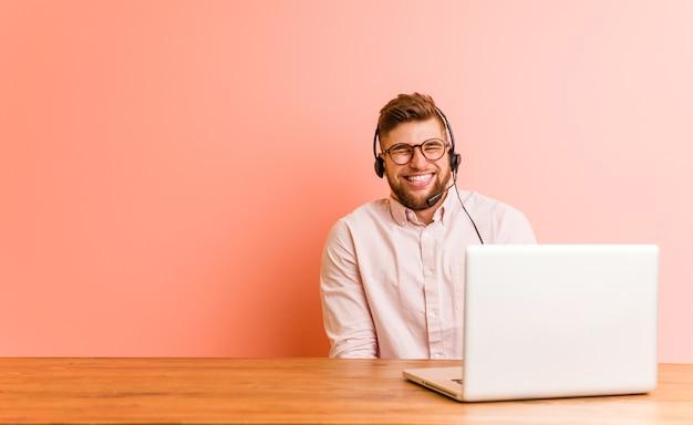 Młody mężczyzna pracujący w call center śmieje się i zamyka oczy, czuje się zrelaksowany i szczęśliwy.