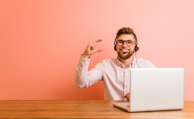 Młody mężczyzna pracujący w call center, trzymając coś z palcami wskazującymi, uśmiechnięty i pewny siebie