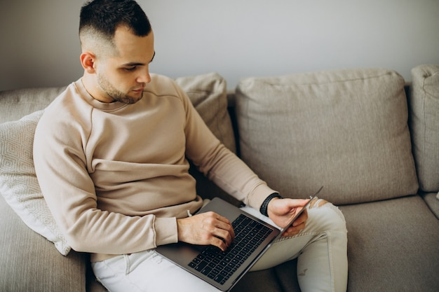 Młody mężczyzna pracujący w domu na laptopie