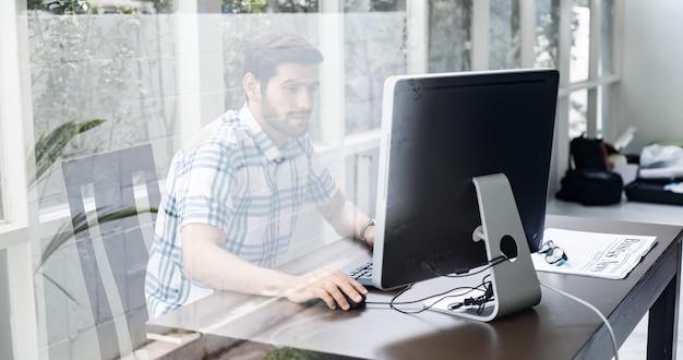 Młody mężczyzna pracujący w domu przez komputer.