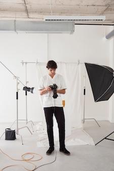 Młody mężczyzna pracujący w swoim studiu fotograficznym