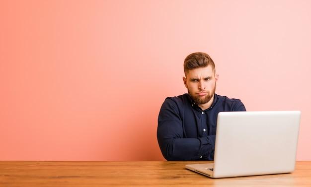 Młody mężczyzna pracujący z laptopem marszczącym brwi z niezadowoleniem, trzyma założone ręce.