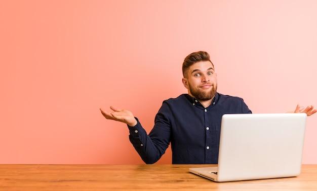 Młody mężczyzna pracujący z laptopem wątpi i wzrusza ramionami w pytającym geście.